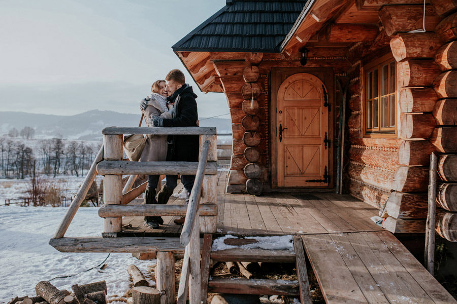 couple outside the wooden cabin