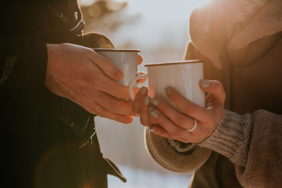 hands holding cups of tea